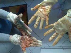 Vier Kinderhände (in Handschuhen) nach dem Eierfärben